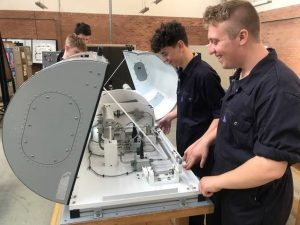 Students fitting aircraft equipment synthetic training rig